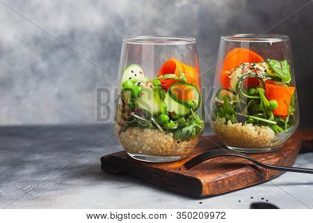 green salad with arugula, carrot,  quinoa, green pease, cucumber, flax and sesame seeds, olive searved on gray background with green linen napkin. top view with copyspace. gorizontal orientation