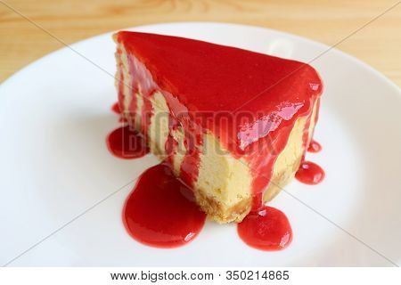Mouthwatering Cheesecake With Vibrant Red Raspberry Sauce On White Plate