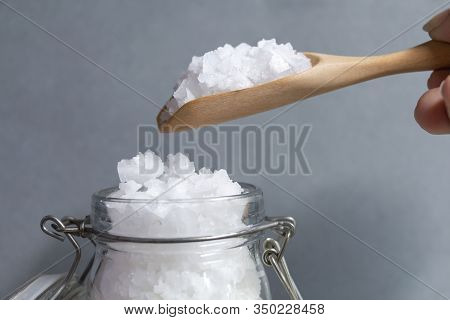 Sea Salt White Crystals In Glass Bottles And On Wooden Spoon In Hand's Woman Is One Of The Main Ingr