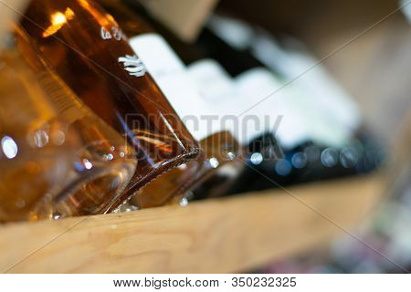 Close Up Of Wine Bottles. Wine Bottles In Wine Store. Macro Of Wine Bottles With Blurred Background.