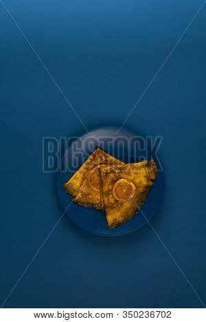 Two Crepe Suzette Pancakes Golden Toasted With Slices Of Orange And In Syrup On A Gravy Stand On A P