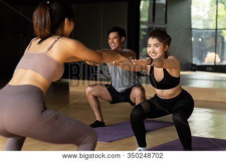 Group Of Happy Asian Women And Man Doing Squat Exercises On Yoga Mats In Aerobics Class. Young Sport