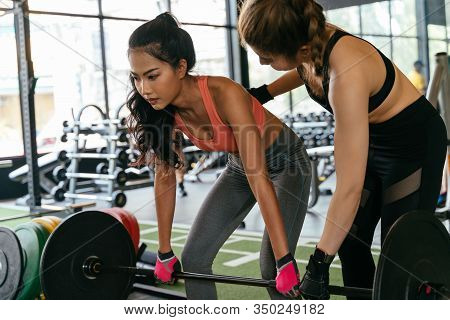 Asian Personal Trainer Coaching A Bodybuilding Woman To Perform The Dead Lifting Exercise With Barbe
