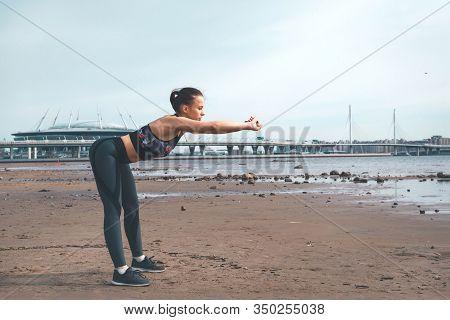 1 White Slender European Girl In Sportswear Leans Forward On The Beach Against The City Background O