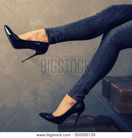Women's Legs In Jeans And High-heeled Shoes On A Wooden Cantilever Ladder