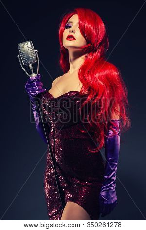 Young Romantic Redhead Woman With Very Long Hair In Red Gown With Microphone On The Stand On A Black