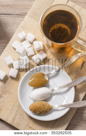 Lump Sugar, Cane Sugar, Loose White Sugar And Buckwheat Honey On A Teaspoon Lie Next To A Glass With