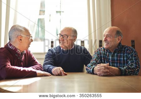 three elderly men argue around a table