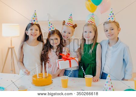 Glad Birthday Girl Stands With Presenet, Happy Friends Come To Congratulate Her, Wear Party Cone Hat