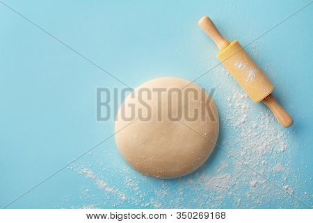 Dough With Flour And Rolling Pin On Blue Background Top View. Bakery Concept. Flat Lay.