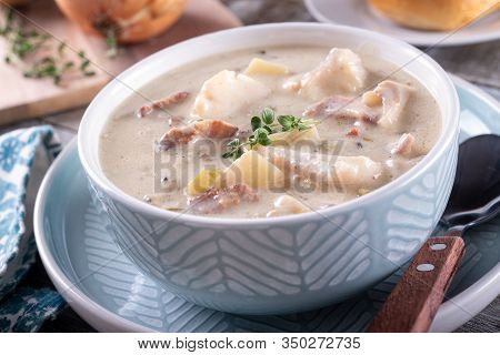 A Bowl Of Delicious Bacon, Haddock And Clam Chowder With Thyme Garnish.