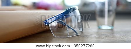 Close-up Of Safety Glasses Lying On Wooden Table. Eye Protector For Industrial, Electrical Or Techni