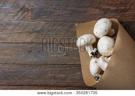 Bunch Of Freshly Picked White Button Mushrooms In Brown Paper Bag On Rustic Wood Table. Plastic Free