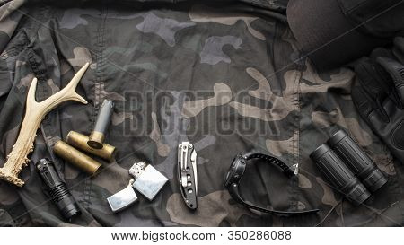 Hunting Accessories On Camouflage Background, Tactical Equipment. Hunting Background. The Concept Of