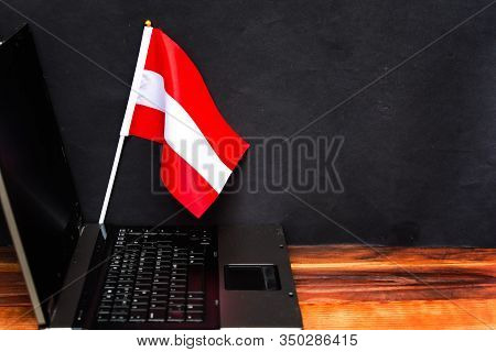 Flag Of Austria , Computer, Laptop On Table And Dark Background