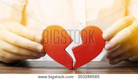 A Man Collects A Red Broken Heart. Valentine's Day Concept. Love And Relationships. Family Psychothe