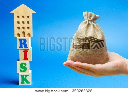 Wooden Blocks With The Word Risk And A Miniature House With Money Bag. Real Estate Investment Risks.