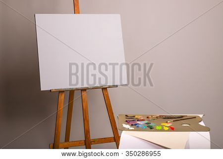 Oil Painting. Easel And Blank Canvas. Palette With Paints And Brushes. Squeeze Out Oil Paints On A P