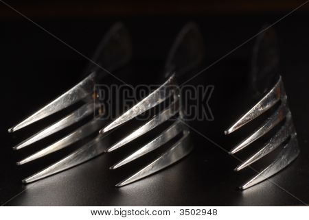 Three forks placed down on table in low light condition poster