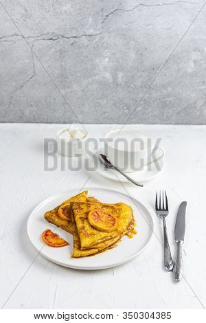 Breakfast, Two Crepe Suzette Pancakes In Orange Sauce And A Cup Of Cappuccino. Still Life Food On A