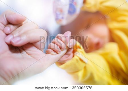 Newborn Baby Touching His Mother Hand, Baby Holding Finger Of His Mother Giving Senses Of Attachment