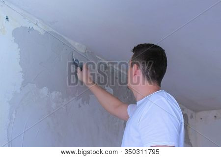 Plasterer Man Spackling Wall With Putty Plaster Aligning Wall. Finishing Construction Renovation Wor