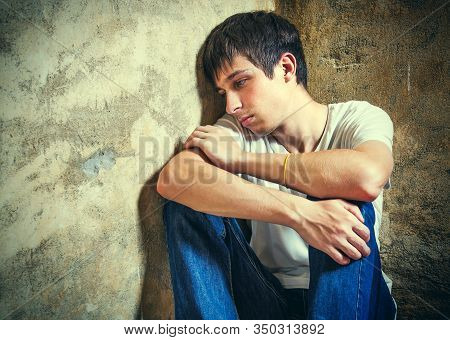 Toned Photo Of Sad Young Man By The Old Wall