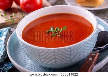 A Bowl Of Delicious Tomato Soup With Thyme Garnish.