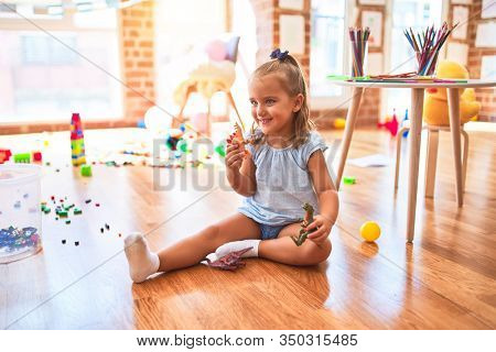 Young beautiful blonde girl kid enjoying play school with toys at kindergarten, smiling happy playing with dinosaurs toys at home