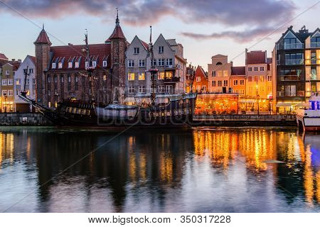 Sightseeing Of Poland. Cityscape Of Gdansk In The Night. Facades Of Buildings And A Ship On The Motl