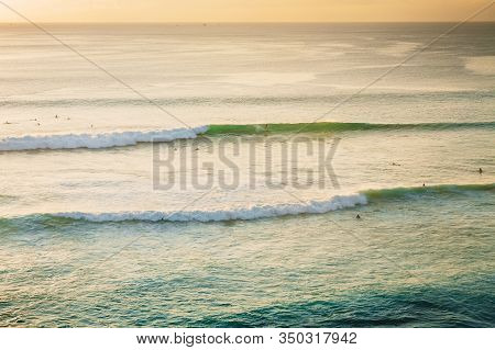 Oceanside With Waves And Surfers At Sunset In Bali