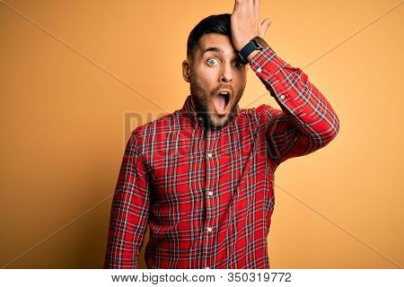 Young handsome man wearing casual shirt standing over isolated yellow background surprised with hand on head for mistake, remember error. Forgot, bad memory concept.