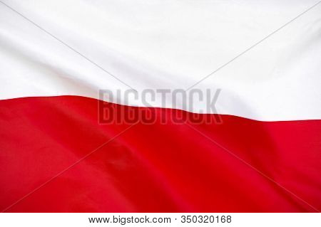 Fabric Texture Flag Of Poland. Flag Of Poland Waving In The Wind. Poland Flag Is Depicted On A Sport