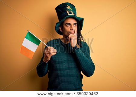 African american man wearing green hat holding irish ireland flag celebrating saint patricks day serious face thinking about question, very confused idea