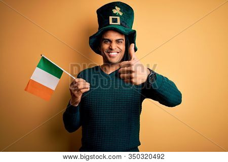 African american man wearing green hat holding irish ireland flag celebrating saint patricks day happy with big smile doing ok sign, thumb up with fingers, excellent sign