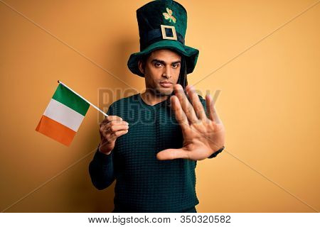 African american man wearing green hat holding irish ireland flag celebrating saint patricks day with open hand doing stop sign with serious and confident expression, defense gesture
