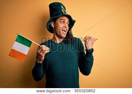 African american man wearing green hat holding irish ireland flag celebrating saint patricks day pointing and showing with thumb up to the side with happy face smiling