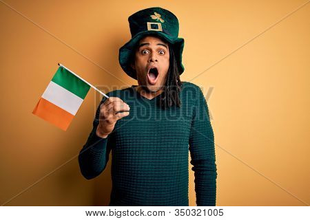 African american man wearing green hat holding irish ireland flag celebrating saint patricks day scared in shock with a surprise face, afraid and excited with fear expression