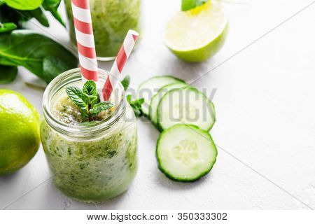 Jars With Green Smoothie And Red Tubules On A Light Background. Freshly Made Vegetable Smoothie. Clo
