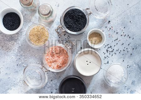 Mix Of Different Salt Types On Grey Concrete Background. Sea Salts, Black And Pink Himalayan Salt Cr
