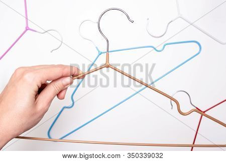Hands Holding Many Colorful Metal Wire Coat, Clothes Hangers On White Background.