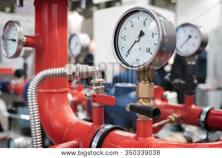 Close Up Of Manometer, Pipe, Flow Meter, Water Pumps And Valves Of Heating System In A Boiler Room