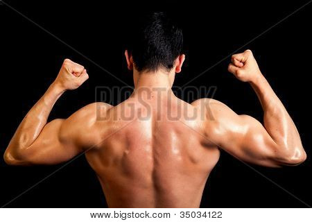 Muscular back of healthy male on black background.