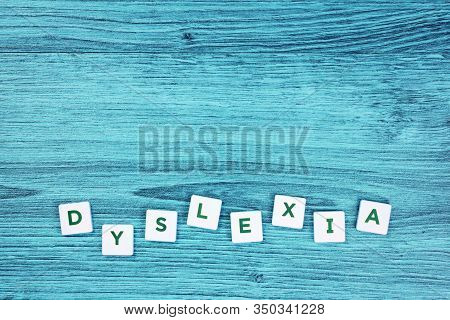 Dyslexia Word Cubes On Blue Wooden Desk Background, Reading Difficulty Awareness And Disorder Concep