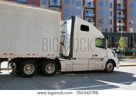 A City On The East Coast Of The Usa. A Large Truck With A Semi Trailer In City Traffic.