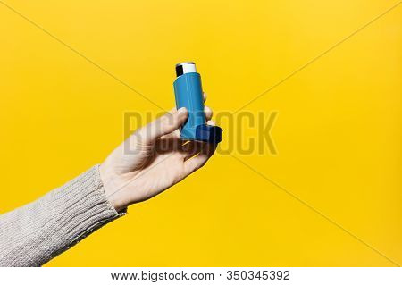 Close-up Of Female Hand Holding Asthmatic Inhaler On Yellow Background.