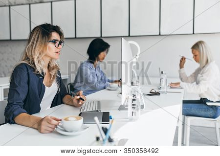 Surprised Blonde Woman Looking At Computer Screen And Enjoying Latte At Her Workplace. Indoor Portra