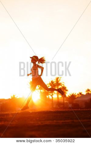 silhouette of a woman athlete running at sunset or sunrise. fitness training of marathon runner.