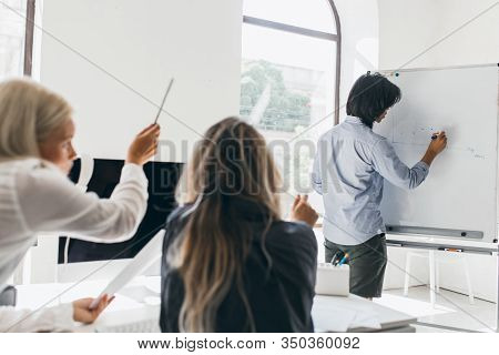 Dark-haired Man Drawing Infographic On Flipchart Standing In Conference Hall. Portrait From Back Of