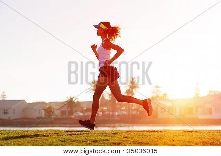 silhouette of a woman athlete running at sunset or sunrise. fitness training of marathon runner.